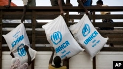 FILE - Workers unload sacks of UNHCR aid supplies at the Al Adala settlement for internally displaced people in Mogadishu, Somalia, Aug.13, 20.