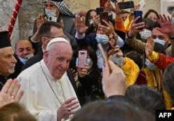 Paus Fransiskus disambut oleh orang-orang saat ia tiba di Gereja Katolik Suriah yang Dikandung Tanpa Noda (al-Tahira-l-Kubra), di kota Qaraqosh (Baghdeda) yang mayoritas beragama Kristen. (Foto: AFP)
