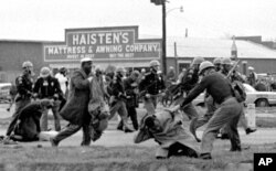 FILE - Alabama state troopers use clubs against voting rights marchers, including John Lewis, shown in foreground, in Selma on March 7, 1965.