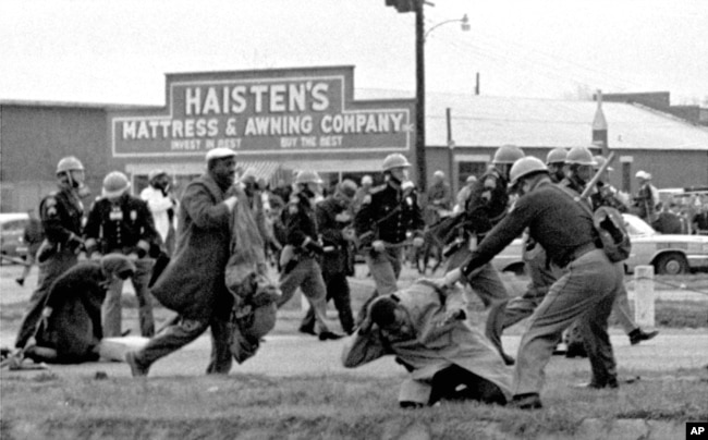 FILE - Alabama state troopers use clubs against voting rights marchers in Selma on March 7, 1965. At foreground right, John Lewis, chairman of the Student Nonviolent Coordinating Committee, is beaten. (Associated Press)