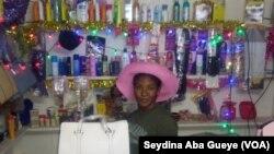 Sophie Diop dans sa boutique devant ses produits cosmétiques, le 26 décembre 2019. (VOA/Seydina Aba Gueye)