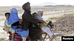 Residents riding on a motorcycle look at U.S. Marines of Police Advisory Team Now Zad, 2nd Battalion, 7th Marines Regiment (not pictured) as they pass an Afghan police checkpoint at Now Zad district in Helmand province, southwestern Afghanistan November 8