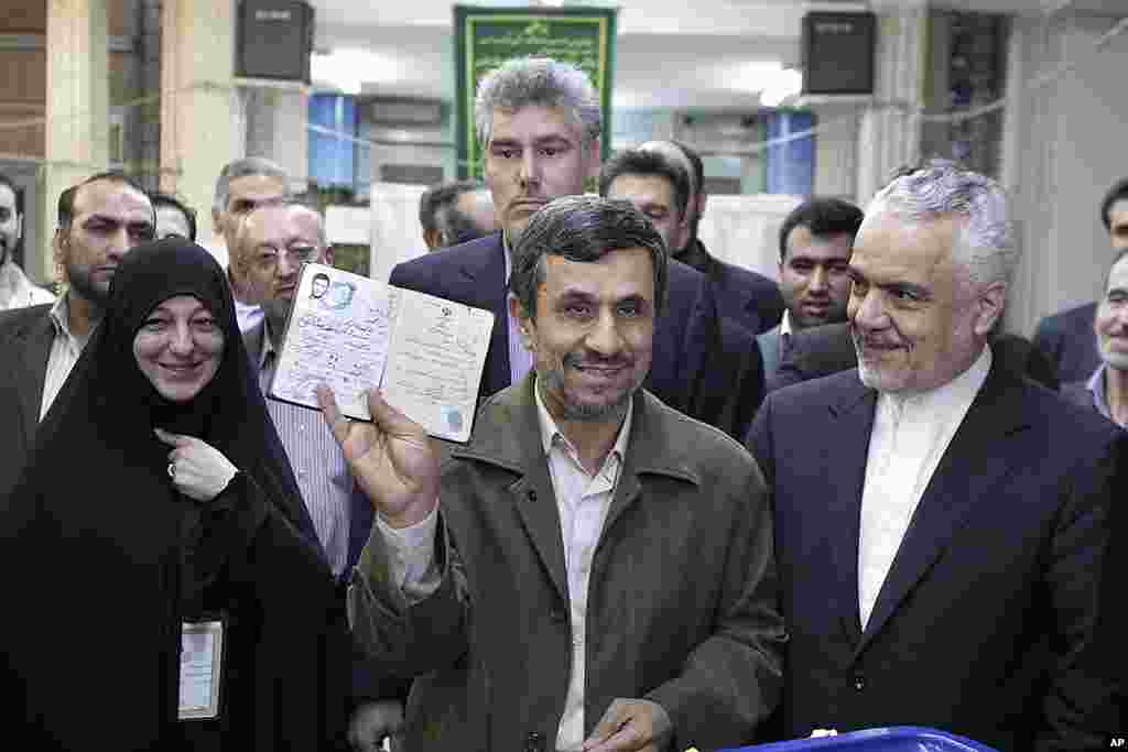 Iranian President Mahmoud Ahmadinejad shows his identification document after casting his ballot for the parliamentary elections at a polling station, while Vice-President Mohammad Reza Rahimi, right, looks on, in downtown Tehran. (AP)