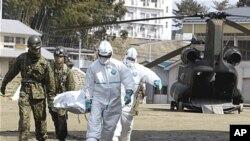 일본 후쿠시마현 니혼마쓰에서 자위대 병력들이 인근 원전 방사선 누출로 방사능에 피폭된 것으로 보이는 한 주민을 들것으로 옮기고 있다.