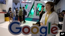 Visitors talk to staff members at a Google stand during the Global Mobile Internet Conference (GMIC) in Beijing, April 28, 2017. Google's search engine and email service remains blocked in mainland China but Chinese companies make use of its ad services to reach a global audience.