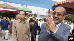 Phnom Penh Governor Kep Chuktema, right, greets well-wishers as he arrives for the inauguration ceremony of Democracy Square in downtown Phnom Penh.