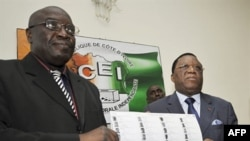 Director of Cote d'Ivoire, Prime Minister Soro's Cabinet: Paul Koffi (L) and President of Ivory Coast's Independent Electoral Commission, Youssouf Bakayoko (R) present the new provisional electoral list ahead of national elections in Abidjan.