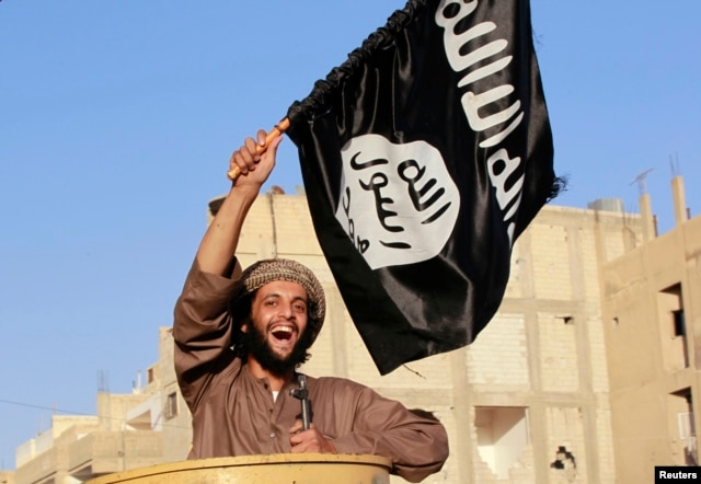 "A militant Islamist fighter waving a flag, cheers as he takes part in a military parade along the streets of Syria's northern Raqqa province June 30, 2014. The fighters held the parade to celebrate their declaration of an Islamic ""caliphate"" after the gro"