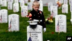 2016年5月30日星期一,来自北卡罗来纳州赫特福德的5岁小男孩克里斯蒂安·雅各布斯穿着像海军陆战队军服的儿童服装,在阿灵顿国家公墓自己父亲的墓碑前驻足停留。