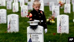 FILE - Christian Jacobs, 5, of Hertford, North Carolina, dressed as a Marine, pauses at his father's gravestone on Memorial Day at Arlington National Cemetery in Arlington, Virginia. on May 30, 2016.
