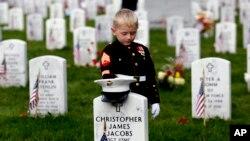 Christian Jacobs (5 tahun) dari Hertford, N.C., berpakaian seperti Marinir, memberi penghormatan di hadapan nisan ayahnya pada Hari Pahlawan (Memorial Day) di Arlington National Cemetery, Arlington, VA, Senin 30 Mei 2016. (Foto: dok).