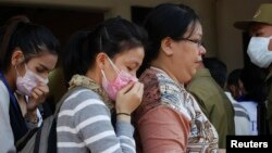 A relative (R) of a victim of a plane crash arrives to a building of a Chinese temple, which is functioning as a temporary mortuary, in Pakse on October 19, 2013.