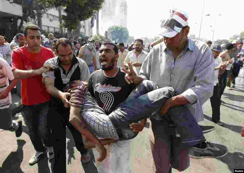 Supporters of former Egyptian President Mohamed Morsi carry an injured man during clashes outside the Republican Guard building in Cairo, July 5, 2013.