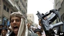 An opposition follower escorting anti-government protesters shouts slogans as he holds up his rifle during a demonstration to demand the ouster of Yemen's President Ali Abdullah Saleh in the southern city of Taiz, July 21, 2011