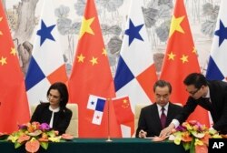 中国外长王毅(右)和巴拿马副总统兼外交部长伊莎贝尔·德圣马洛在北京签署两国建立外交关系的联合公报。(2017年6月13日)