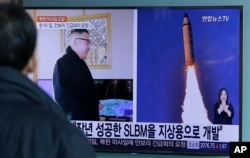 "FILE - A man watches a TV news program showing photos published in North Korea's Rodong Sinmun newspaper of North Korea's ""Pukguksong-2"" missile launch and North Korean leader Kim Jong Un at Seoul Railway Station in Seoul, South Korea, Feb. 13, 2017."
