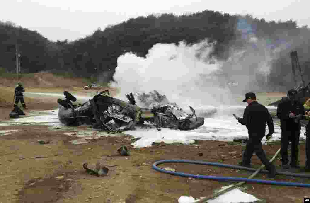 "A firefighter tries to extinguish a U.S. Marine helicopter after it made a ""hard landing"" during an exercise, north of Seoul, April 16, 2013."