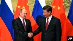 Presiden Rusia Vladimir Putin (kiri) dan Presiden China Xi Jinping berjabat tangan dalam pertemuan di Beijing, Juni 2016.