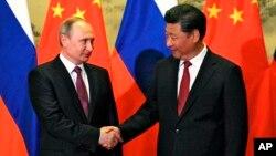 Presiden Rusia Vladimir Putin (kiri) dan Presiden China Xi Jinping dalam pertemuan di Beijing tahun lalu (foto: dok).
