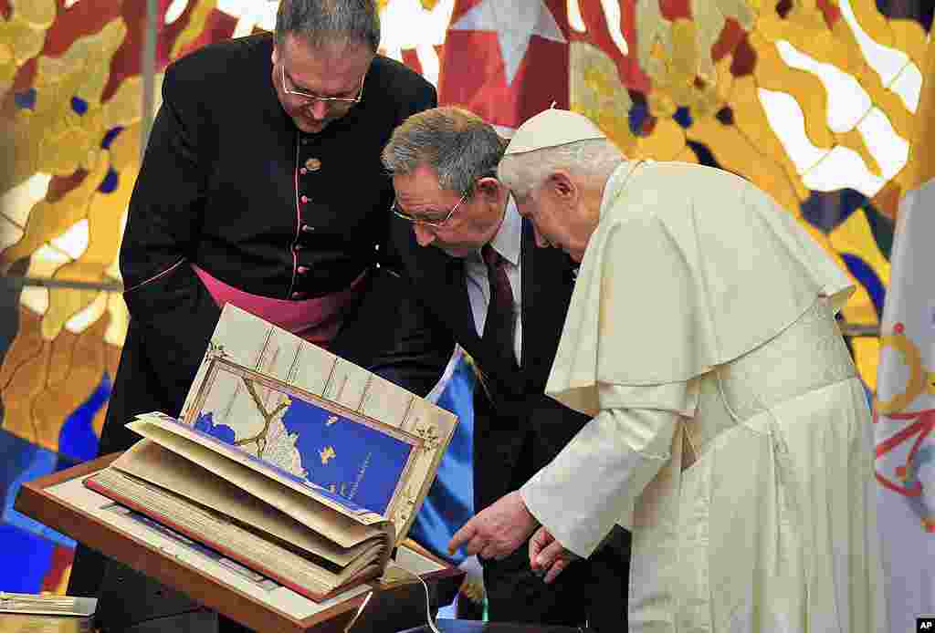 Pope Benedict presents a replica of Tolomeus Geography book to Cuba's President Raul Castro, center, during a meeting in Havana. (AP)