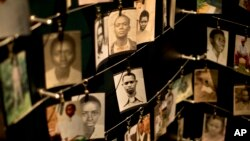 FILE - Family photographs of some of those who died in the Rwandan genocide hang in a display in a memorial center in Kigali, Rwanda, April 5, 2014.
