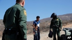 FILE - A Guatemalan father and son, who crossed the U.S.-Mexico border illegally, are apprehended by U.S. Border Patrol agents in San Diego, California, June 28, 2018.