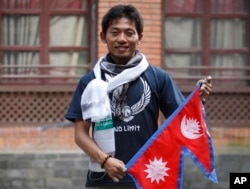 Japanese climber Nobukazu Kuriki poses with a Nepalese flag during a press conference in Kathmandu, Nepal, Sunday, Aug. 23, 2015.