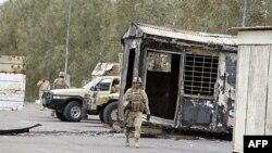 Binh sĩ Iraq đứng gác gần 1 xe kéo bị đốt cháy ở Trại Ashraf, phía bắc Baghdad, Iraq, 8/4/2011