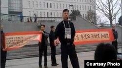 袁冬等人2013年3月31日在北京西单展示反腐横幅,征集签名呼吁官员公示财产。(网络图片)