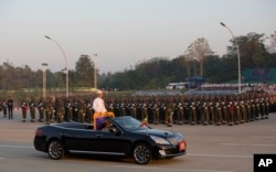 FILE - Myanmar's President Thein Sein, standing in an open vehicle, inspect officers and soldiers during a ceremony to mark the 67th anniversary of Independence Day in Naypyitaw, Jan. 4, 2015.