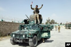 FILE - An Afghan soldier raises his hands as a victory sign, in Kunduz city, Oct. 2, 2015.