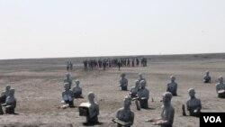 Patung penyintas dengan latar belakang warga penyintas yang melakukan ziarah makam leluhur, Minggu, 24 Mei 2015. (VOA/Petrus Riski)