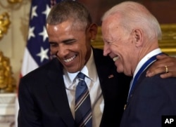 FILE - President Barack Obama laughs with Vice President Joe Biden during a ceremony in the State Dining Room of the White House in Washington, Jan. 12, 2017.