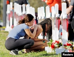 FILE - A senior at Marjory Stoneman Douglas High School weeps in front of a cross and Star of David while a fellow classmate consoles her at a memorial by the school in Parkland, Florida, Feb. 18, 2018.