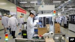 រូបឯកសារ៖ បុគ្គលិកក្រុមហ៊ុនទូរស័ព្ទ Huawei នៅក្នុងរោងចក្រក្នុងទីក្រុង Dongguan ប្រទេសចិន កាលពីខែមីនា ២០១៩។