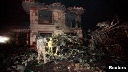 Các lực lượng an ninh Iraq kiểm tra hiện trường vụ đánh bom xe tải tự sát tại một trạm xăng ở thành phố Hilla, phía nam Baghdad, Iraq, ngày 24 tháng 11 năm 2016.