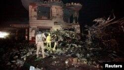 Pasukan keamanan Irak memeriksa lokasi serangan bom mobil di Hilla, selatan Baghdad, Kamis (24/11).