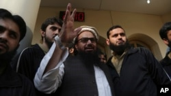 FILE - Hafiz Saeed, head of the Pakistan's Jamaat-ud-Dawa group, waves to supporters at a mosque in Lahore, Pakistan, Nov. 24, 2017.