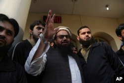 FILE - Hafiz Saeed, head of the Pakistan's Jamaat-ud-Dawa group waves to supporters at a mosque in Lahore, Pakistan, Nov. 24, 2017.