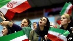 Perempuan Iran melambai-lambaikan bendera Iran dalam upacara melepas tim sepakbola negara itu ke Piala Dunia 2014, di stadiun Azadi di Teheran, Juni 2014. (AP/Ebrahim Noroozi)