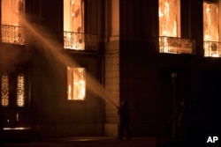 Firefighters spray the flames at the 200-year-old National Museum of Brazil, in Rio de Janeiro, Brazil, Sept. 2, 2018.