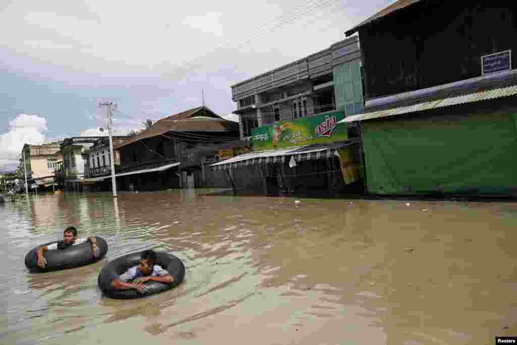 Men wade along a flooded street in Kalay township, Sagaing region, Aug. 2, 2015.