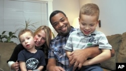 "Damon Brown sits with his wife, Bethany, as they hold their sons Theo, 3, left, and Julian, 5, at their home in Seattle. Damon Brown found a kidney on Facebook after telling his story on a special page the Seattle dad created under the name, ""Damon Kidney"