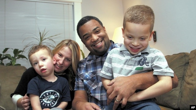 """Damon Brown sits with his wife, Bethany, as they hold their sons Theo, 3, left, and Julian, 5, at their home in Seattle. Damon Brown found a kidney on Facebook after telling his story on a special page the Seattle dad created under the name, """"Damon Kidney"""