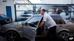 FILE - Taxi driver Michael Villegas pushes his car to keep his place in a line of drivers waiting to buy new car batteries in Caracas, Venezuela, Aug. 6, 2015. Drivers faced a gasoline shortage a week ago in the South American OPEC nation.