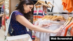 Woman looking through clothes in shopping mall