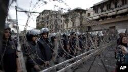 Cảnh sát chống bạo động Ai Cập đứng gác sau hàng rào dây thép gai tại Cairo, ngày 4/12/2012.