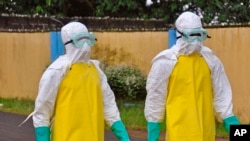 FILE - Health workers wearing protective gear go to remove the body of a person who is believed to have died after contracting the Ebola virus in the city of Monrovia, Liberia, Saturday, Aug. 16, 2014.