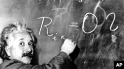 FILE - Dr. Albert Einstein writes out an equation for the density of the Milky Way. The satellite launched Monday will test the concept that in a vacuum, all bodies fall at the same speed -- an idea on which Einstein based the theory of general relativity that made him famous.