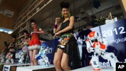 FILE - Humanoid robots called Nao, developed by a French company, Aldebaran Robotics, dance along with models to mark the opening of a press conference of the Manufacturing Expo in Bangkok, June 19, 2012.